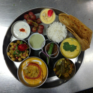 Our Awadhi Thali (clockwise from right): sultani dal, Awadhi-style okra dum, stuffed tomato in shahi gravy, sweet potato chaat, tomato-onion-cucumber raita, fruit, mango kulfi, basmati rice, parantha. Center: veg seekh kabab, hara bhara kabab, and special chutney.